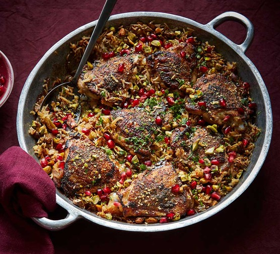 Crispy za'atar chicken pilaf with pomegranate served in a large casserole dish