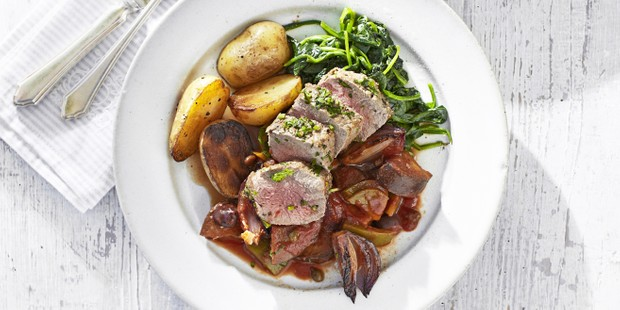 A white plate of seared lamb, potatoes, wilted greens and red onion wedges