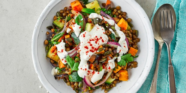 A big bowl full of brown lentils, cubed sweet potato, red onion, greens and a white dressing