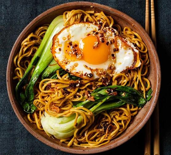 Noodles with crispy chilli oil eggs in a ceramic bowl