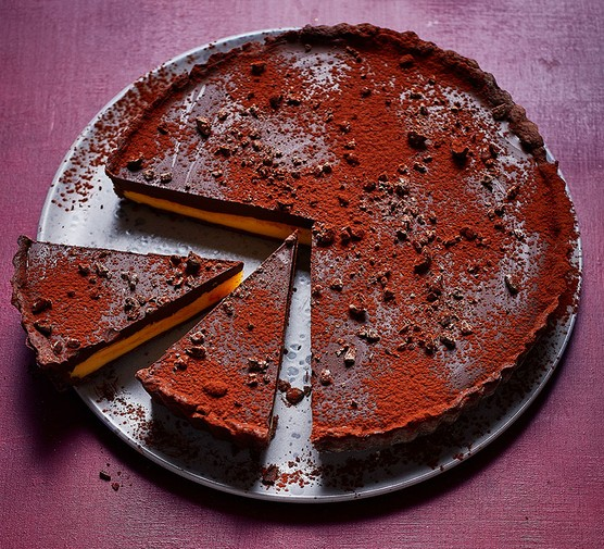 Dark chocolate and passionfruit tart with two slices cut out