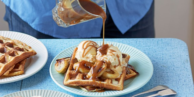 Waffles topped with ice cream, bananas and salted caramel sauce