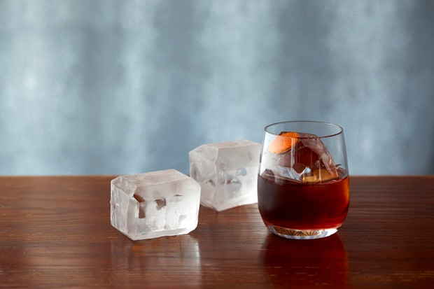 A negroni cocktail places next to large ice cubes