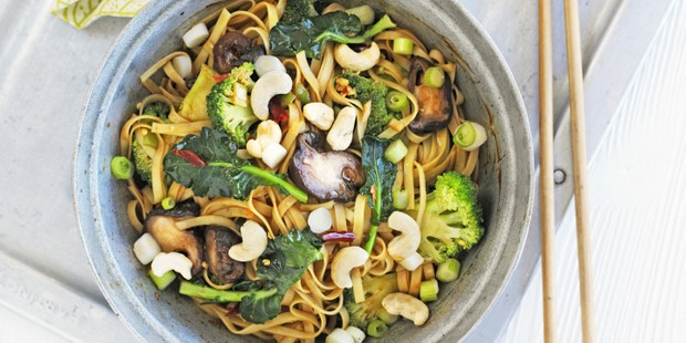 A frying pan full of noodles, mushrooms and broccoli