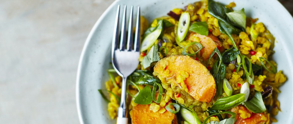 A bowl full of sweet potato dhal with spring onions on top
