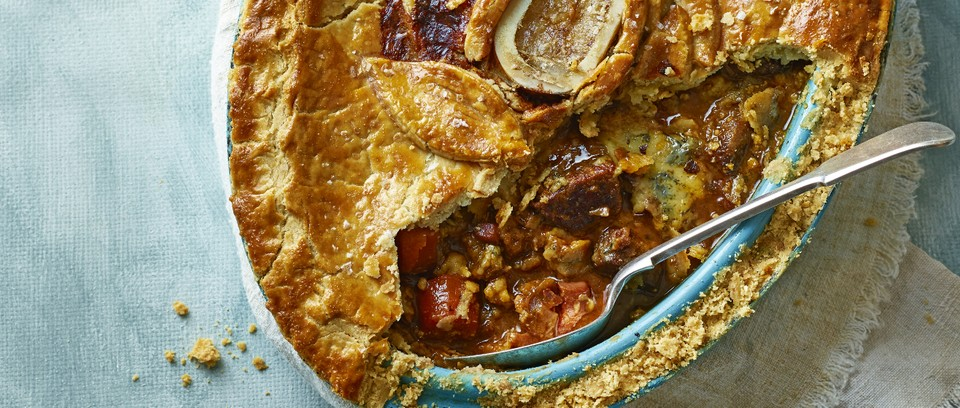 A pastry-topped steak pie with a serving spoon in it