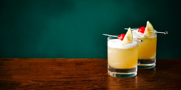 Two brandy sour cocktails against a green background