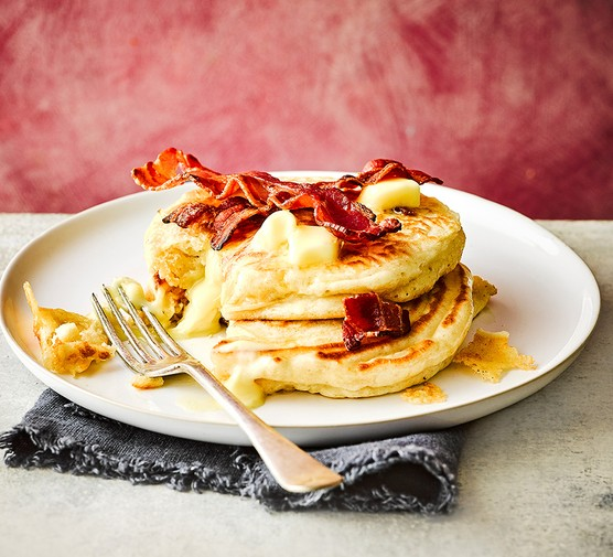 A plate with brie-stuffed pancakes with crispy bacon