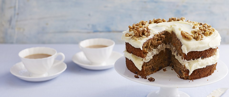 A frosted carrot cake with a cup of tea on the side