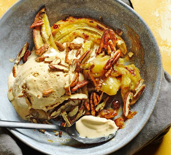 Boozy baked caramelised bananas in a bowl with ice cream