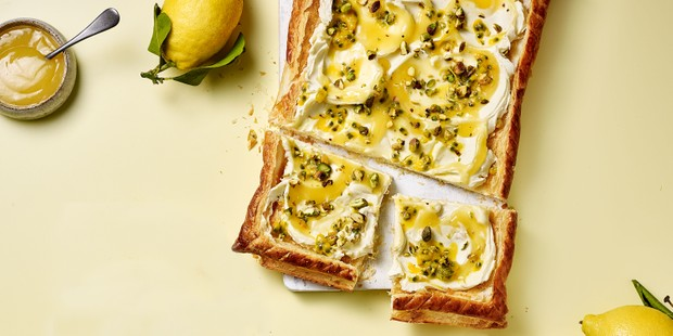 Lemon, mascarpone and passion fruit puff pastry tart on a board, with lemons