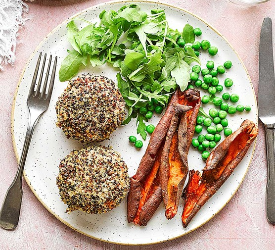 Quinoa-coated salmon and sweet potato fishcakes on a plate with peas