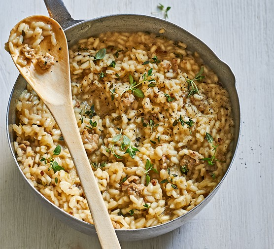 Pot of sausage and fennel risotto with wooden spoon