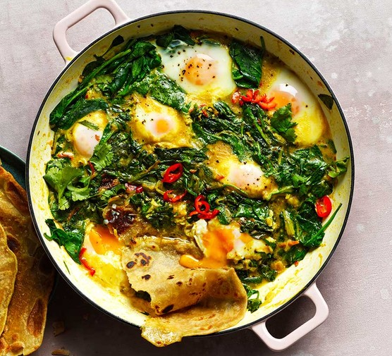 Spinach, coconut & turmeric baked eggs with paratha in a large baking dish