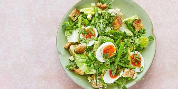 Egg and greens salad in bowl with croutons