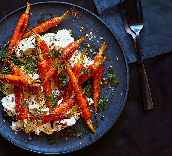 Roasted spiced carrots & labneh on a blue plate