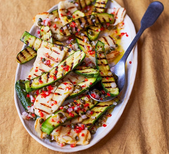 Grilled courgette & halloumi salad with caper & lemon dressing on an oval plate