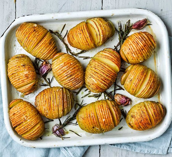 Hasselback potatoes in a baking dish with rosemary