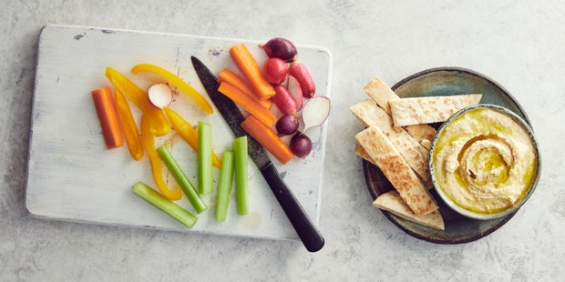 Pot of hummus with crackers and vegetable batons