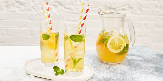 Two glasses and a jug of iced tea with lemon slices and mint sprigs