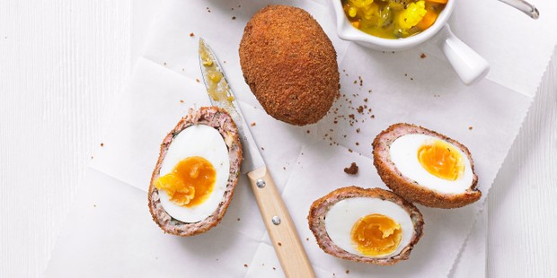 Scotch eggs, halved and served with pickle