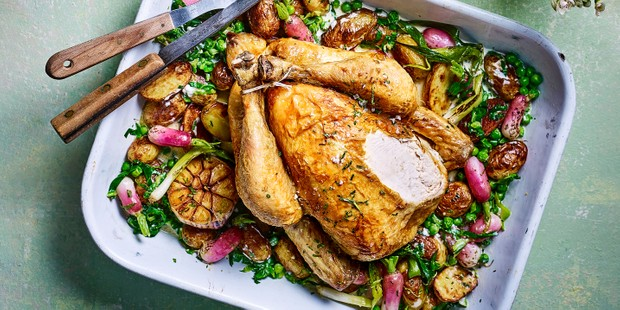 Spring roast chicken on a bed of vegetables in a traybake