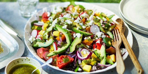 Plate loaded with colourful tomato avocado, feta salad