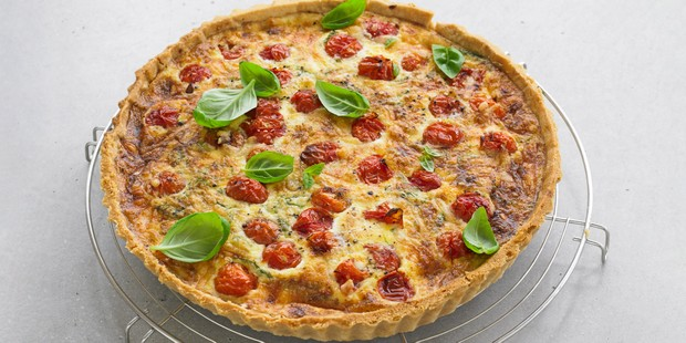 Whole quiche topped with tomatoes and basil