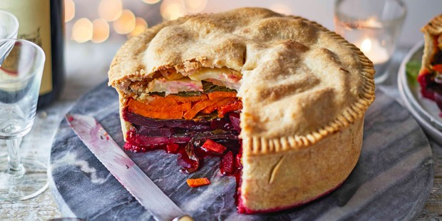 Vegan pie cut open to reveal colourful layered veg