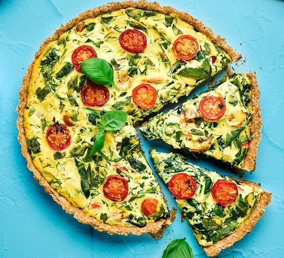 Vegan spinach & cherry tomato quiche cut into slices
