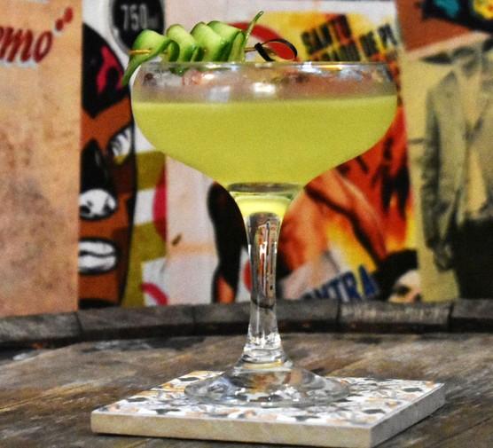 Dizzy mezcal cocktail on bar with cucumber garnish