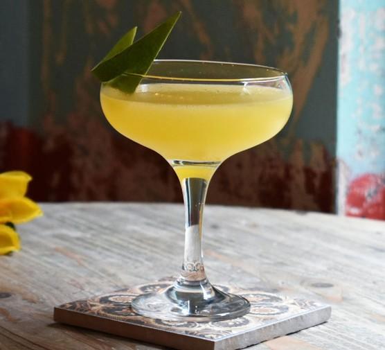 Mezcal mangarita cocktail in glass with peel garnish