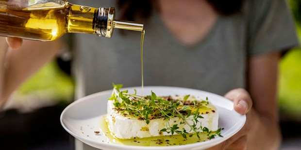 Close-up of woman pouring olive oil over sheep cheese on plate