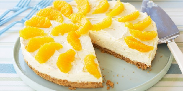 Orange cheesecake on plate with slice cut