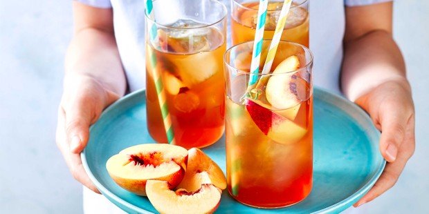 Peach iced tea in glasses on tray with straws