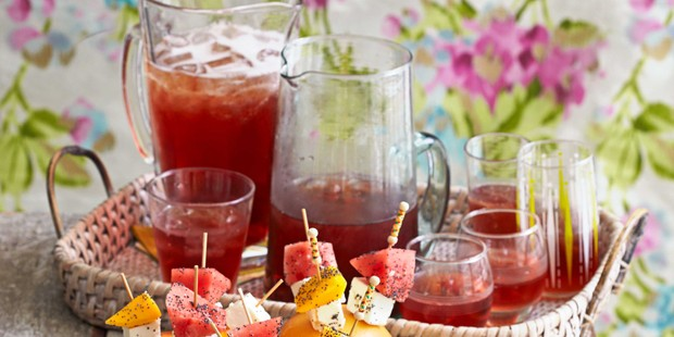 Rum punch in glasses and pitcher on tray