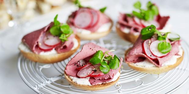 Salt beef on mini bagels on rack