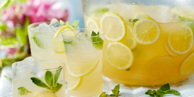 Summer punch with lemon slices in glasses and bowl