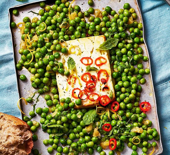 Baked feta with peas, chilli & preserved lemon on a baking tray