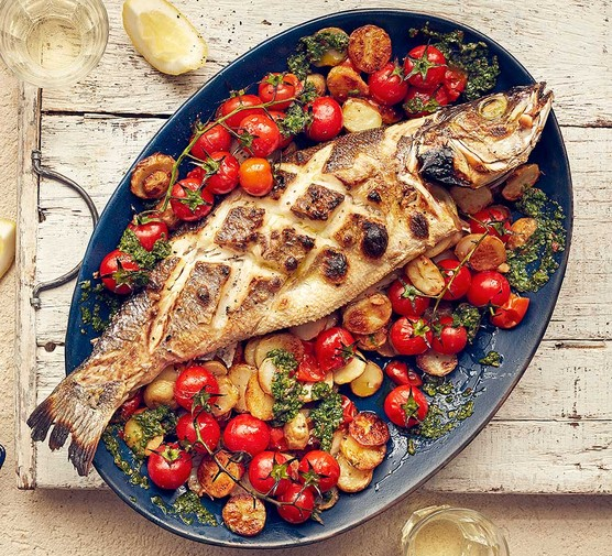 Whole baked fish with watercress and chilli salsa served on a plate