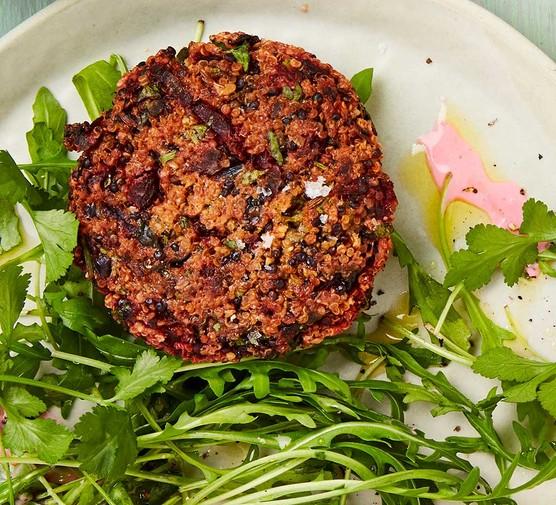 One vegan beetroot & quinoa burger on a rocket salad