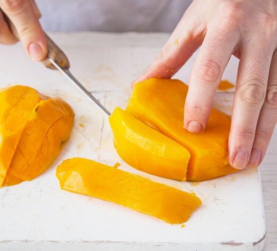Cutting a mango into thin slices