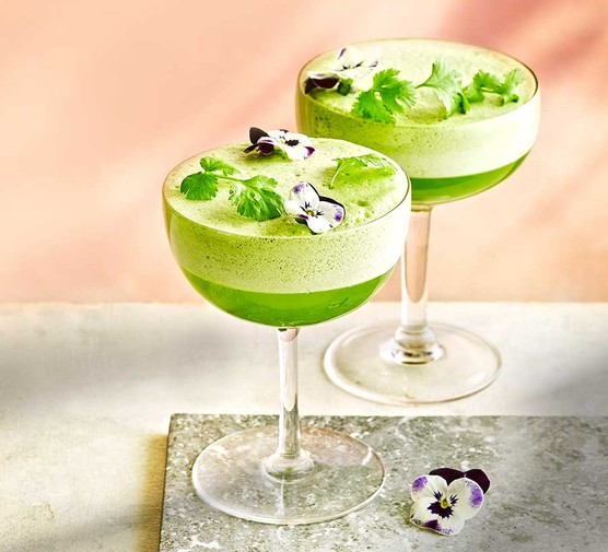 Two cocktail glasses serving green juice pisco sour