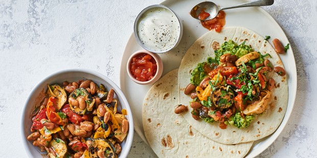 Fajita wraps loaded with vegetables, beans and sauces in pots