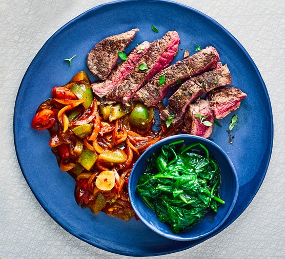 Bowl of steak strips with vegetable stew and spinach in a pot