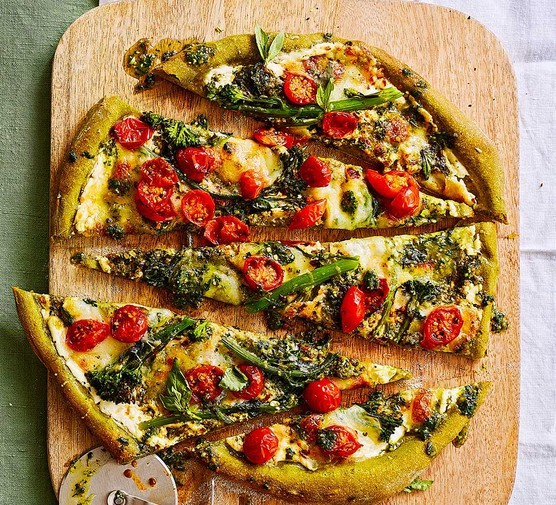 Punchy spinach pesto pizza cut into pieces and served on a board