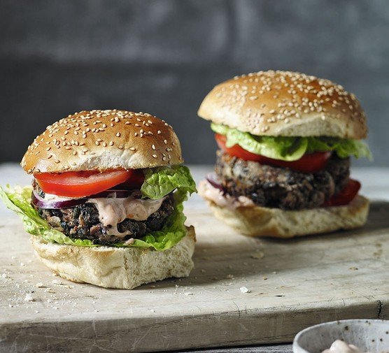 Two black bean veggie burgers on a serving board