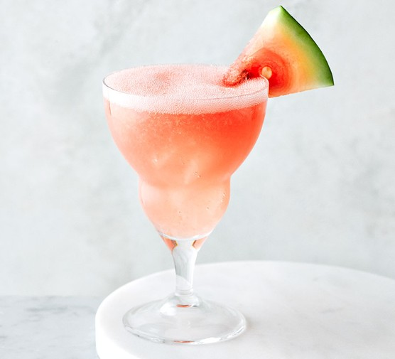 Watermelon daiquiri served in a cocktail glass with a wedge of watermelon