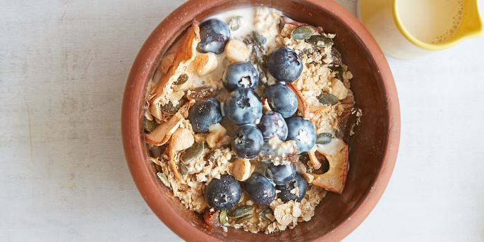 A ceramic bowl of muesli topped with blueberries