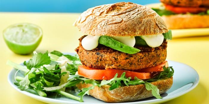 A veggie burger with salad and avocado